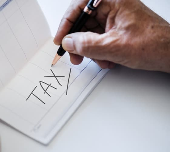 A picture of a man writing tax on a piece of paper