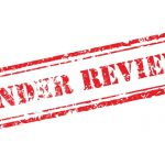 IR35 tax review concept shown by Under review rubber stamp